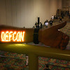 """From the vantage point of Defcon's """"Wireless Village"""" in a skybox above the main conference level, one attendee flaunts his homemade laser text and image projector. The text was readable clearly, even when projected to the far wall at the end of the hall in this photo."""