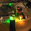 """A homebuilt laser projector, made from off the shelf commercial parts, is mounted inside a plastic storage box of the kind you might see in a """"99 cents"""" store."""