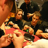In the lockpick village area, Defcon attendees crowd the tables for instruction in how to pick locks. These people are in a timed contest to see who can take apart a lock cylinder then put it all back together correctly.