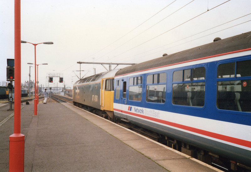 Work extending the electrification through to Kings Lynn is seen here at Cambridge on 22/04/89 as 47458 takes over a Liverpool Street service for Kings Lynn.