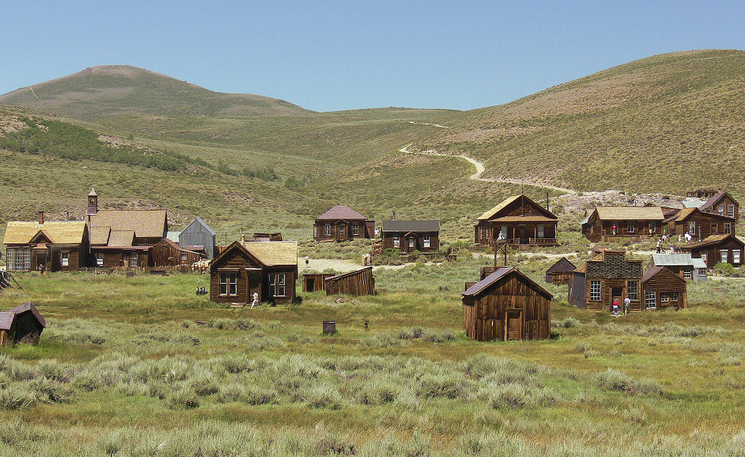 "Only 10% of the original town remains--there were major fires in 1892 and 1932--but what's left makes this the quintessential Wild West ""ghost town"". This view looking west shows, from left, the house of James S. Cain, principal property owner of Bodie; the towered Methodist Church; and various residences. The 2 buildings in the right foreground are the firehouse and the Sam Leon Bar and Barber Shop. The main road out of Bodie, 10 miles of pavement then 3 miles of dirt, snakes off in the distance."