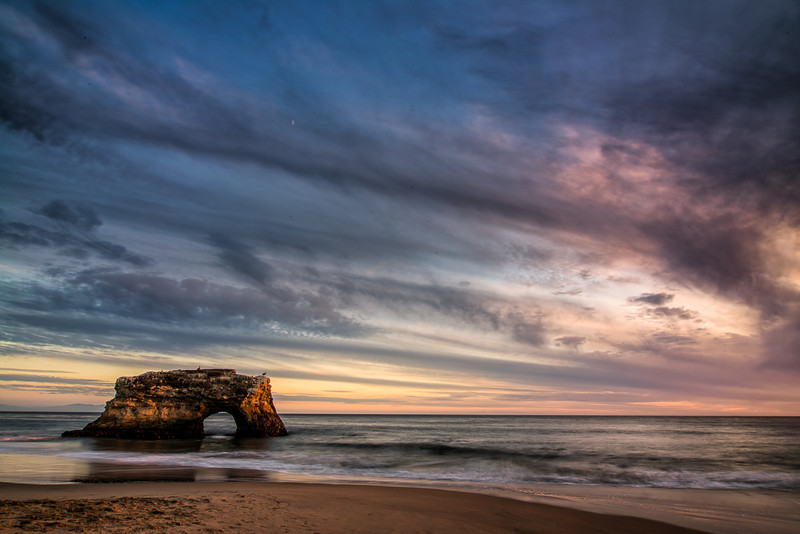 An approaching storm provides beautiful sunset colors at Natural Bridges State Beach in Santa Cruz, CA.