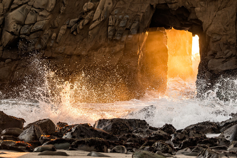 Waves crashing on beach rocks in front of the arch on Pfeiffer Beach.
