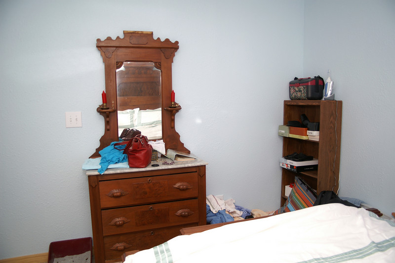 The dresser has a marble top and a piece above the mirror to match the bed.