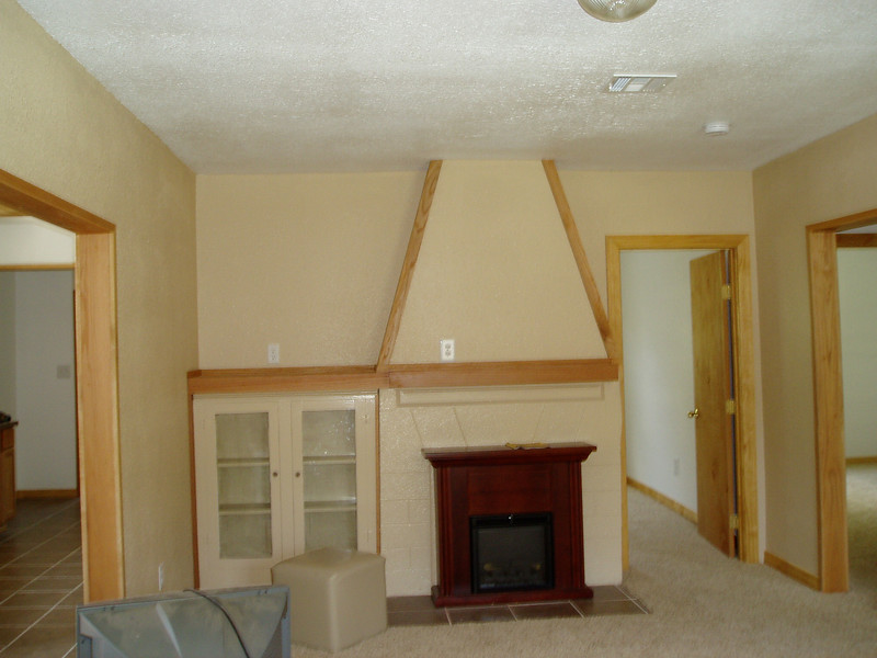 """First off, the godawful, ugly, fake, cheesy electric """"fireplace"""" is going bye-bye.  This is the living room shot from the opposite end of the room. You can see the kitchen/dining off to the side and the other entrance to my office."""