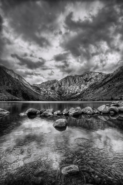 Convict Lake My first visit there. I love that feeling of the first time... your heart quickens, your eyes get all sharp and darty at the new sights, even my stomach jumps around a little at the excitement of NEW.   I'm big on the story too - and I love hearing them about the places I visit. Convict Lake was named after an incident in 1871, where a group 'o thugs, er, 'convicts' escaped from prison in Carson City. That's 200 miles away. So a buncha lawmen, er, a 'posse' chased those buggers all the way down here, where they had a shootout. The sheriff was killed, as was his Indian guide. They named the lake after the convicts, the mountain (Mt. Morrison) after the sheriff. Nobody named anything after the Indian guide, which strikes me as just pure ungrateful.   It was a moody, weathery day... kinda fitin' with the story that goes with it. But I just went with the vibe and took this picture to share with y'all.