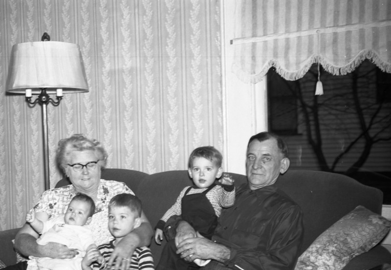 """Grandma & Grandpa Collins with Mark, John, & me.  Grandpa's """"Bad"""" below his left eye are noticable in this photo.  This was taken in their Living Room at 210 East Bryn Street in Troy, Illinois."""