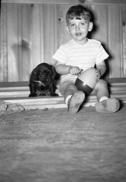 This photo shows me sitting in the Living Room at our home at 213 South Main Street.  Though I don't remember him, the dog pictured must be Jake, one of two dogs that I had during my childhood.  We didn't have Jake for long because he met with an accident, but he certainly is a pretty dog.  I have no memory of him, so I was delighted to find this photo.