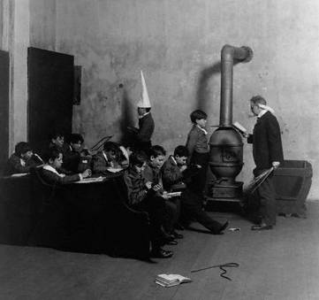 1905 --- Boy in Dunce Cap Sitting in Corner of Classroom --- Image by © CORBIS