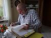 Rainier goes through a binder of family genealogy nformation.