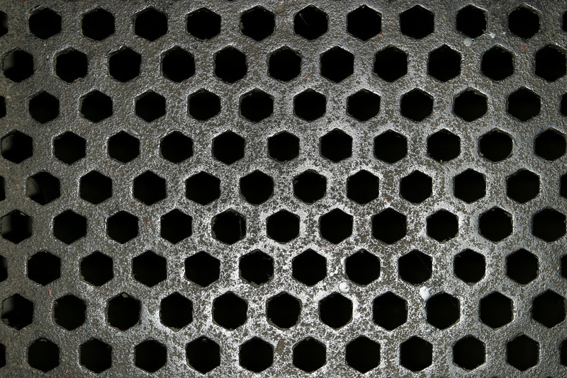 A steel floor grid from Kilmainham Jail in Dublin against a black background. The hexagonal pattern repeats throughout the image although the area in the center is polished through wear and tear.