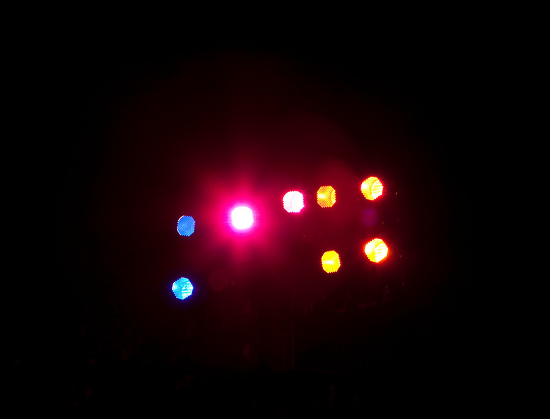 A group of spotlights illuminating a stage with a bit of lighting flare.
