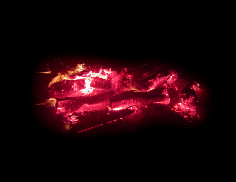 Logs burning with red hot embers in a camp fire pit on Cannon Beach.