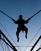 A black silhouette of a boy jumping and being suspended in mid-air by bungee cords.