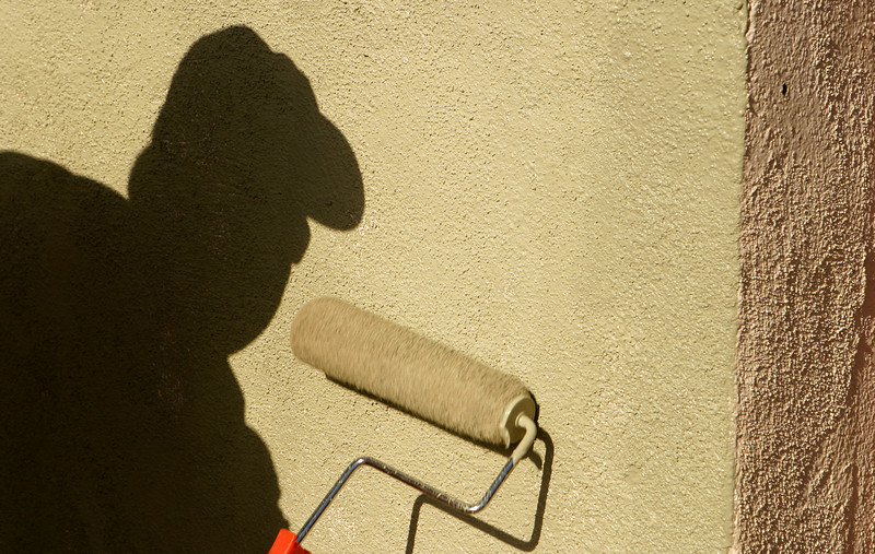 A painter's shadow against a wall as he paints the wall with a paint roller. (Note: The paint roller has a little bit of motion blur as it is actively being rolled over the wall surface.)