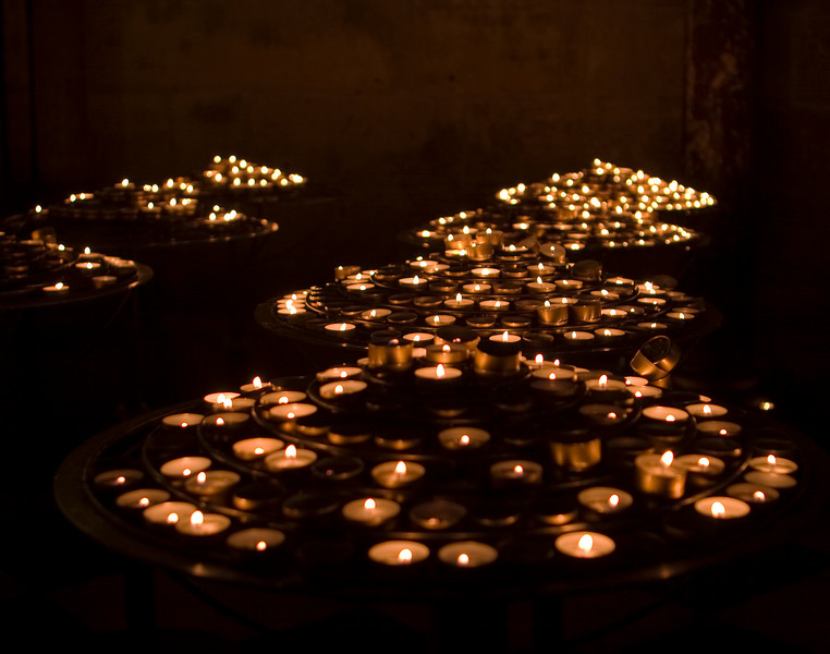 Hundreds of little tea light candles are lit at Notre Dame cathedral in Paris to give emphasis to people's prayers. The candles were flickering through the exposure which results in a soft image.