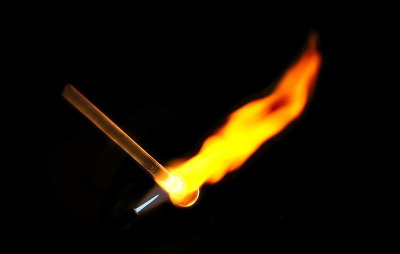 A blow torch with a blue flame heating up a glass rod to the melting point. The flame spreads out into an orange glow after it heats the glass.