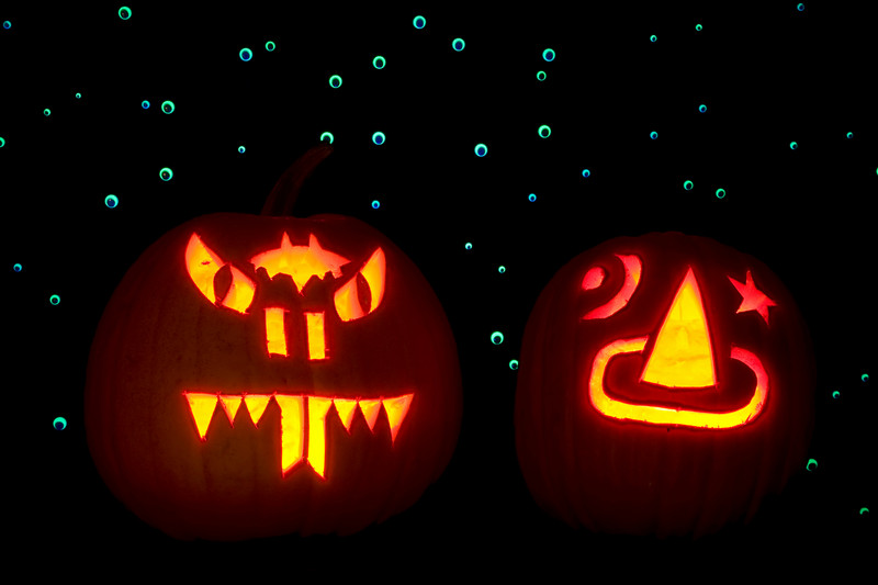 Two carved pumpkins, lighted with candles, are placed in front of a backdrop of hundreds of googly eyes that are lit up with ultraviolet light. One pumpkin is carved as a snake and the other with a sorcerer's hat.