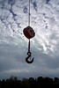 A hook used to lift boats out of water is suspended over the horizon from a piece of tacke. It is almost silhouetted against a dramatic cloudy sky.