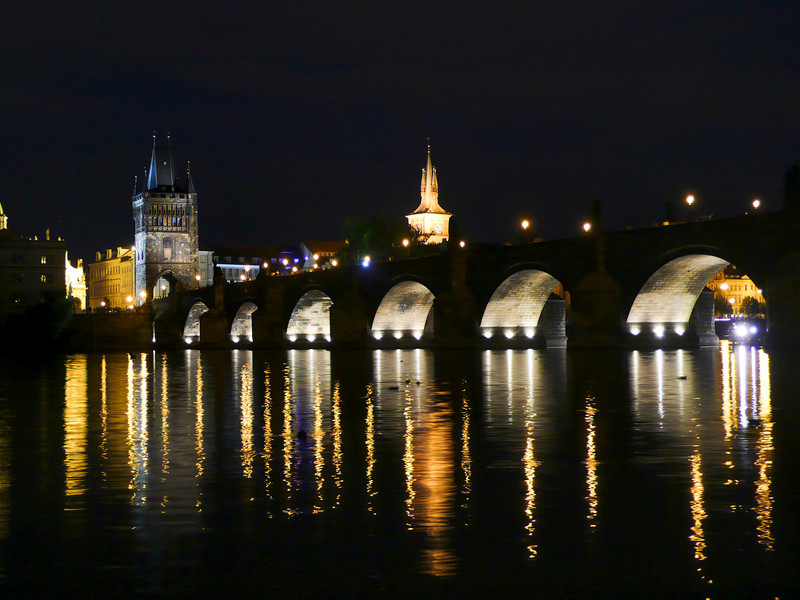 A view of Charles Bridge and the Old Town of Prague at night with reflections off the Vltava River. This is a romantic location to view the bridge.