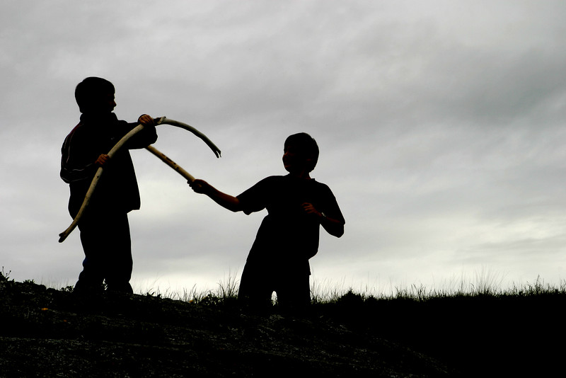 Two boys are dueling with sticks near a beach in Washington State. They are outlined by the cloudy sky in the background.