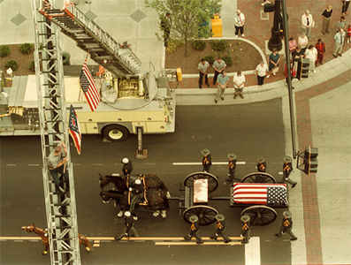 The caisson carrying the casket of John Holcomb passes underneath an arch formed by ladders of Hamilton firetrucks, with firemen on each ladder holding the flags of the US and Ohio.<br /> e.l. hubbard foto