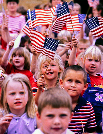 Marshanna McClellan, 6, center, and her Pierce Elementary School classmates wave American flags during the school's Red, White, and Blue Day honoring Veterans from the Lindenwald area.<br /> e.l. hubbard foto