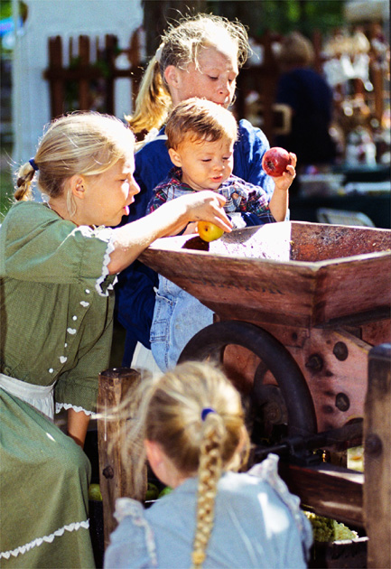 Dropping apples into the apple cider press Sunday at Pioneer Days at Governor Bebb Preserve are sisters Hannah, 10, and Megan, 12, Ellinghausen, with some help from Dakota Kiefer, 18 months.  Another sister, Allison, 7, turns the crank.  All four family members are from Ross.  <br /> E.L. Hubbard/Journal-News