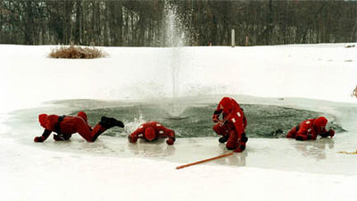 Hamilton Fire and Rescue personnel crawl out onto the ice from a frozen pond during a rescue training session Friday, 1/15/99 at Hickory Woods subdivision.<br /> e.l. hubbard foto