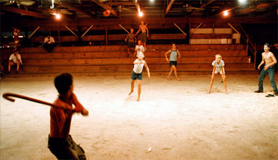 The girls versus the boys in a game of baseball, with a cane for a bat, in an empty barn at the fair Thursday night.<br /> e.l. hubbard foto