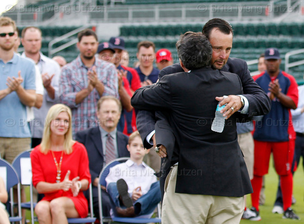 FORT MYERS, FL, Feb. 17, 2012: Boston Red Sox pitcher Tim Wakefield, second from right, hugs Red Sox chairman Tom Werner as teammates, friends and family watch as he prepares to announce his retirement from baseball after 19 Major League seasons. (Brita Meng Outzen/Boston Red Sox)