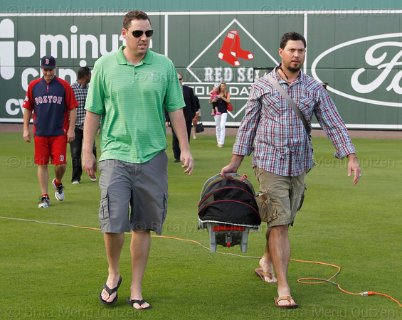 FORT MYERS, FL, Feb. 17, 2012: Boston Red Sox pitcher Josh Beckett, right, toting an infant carrier with his baby girl inside, and pitcher John Lackey walk onto the field to support teammate Tim Wakefield during his retirement announcement. (Brita Meng Outzen/Boston Red Sox)