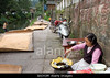 M469, TA12.9 <br /> Choice 3 of 8<br /> <br /> BAJX0M An old woman frying potatoes at the a walkway at the side of a river for people to snack on in rural China.