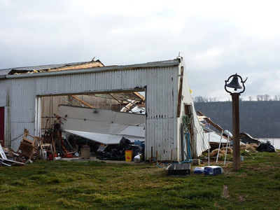 The shop is destroyed.  The hill in the background is across the river.  You can see the path of the tornado where trees are downed.