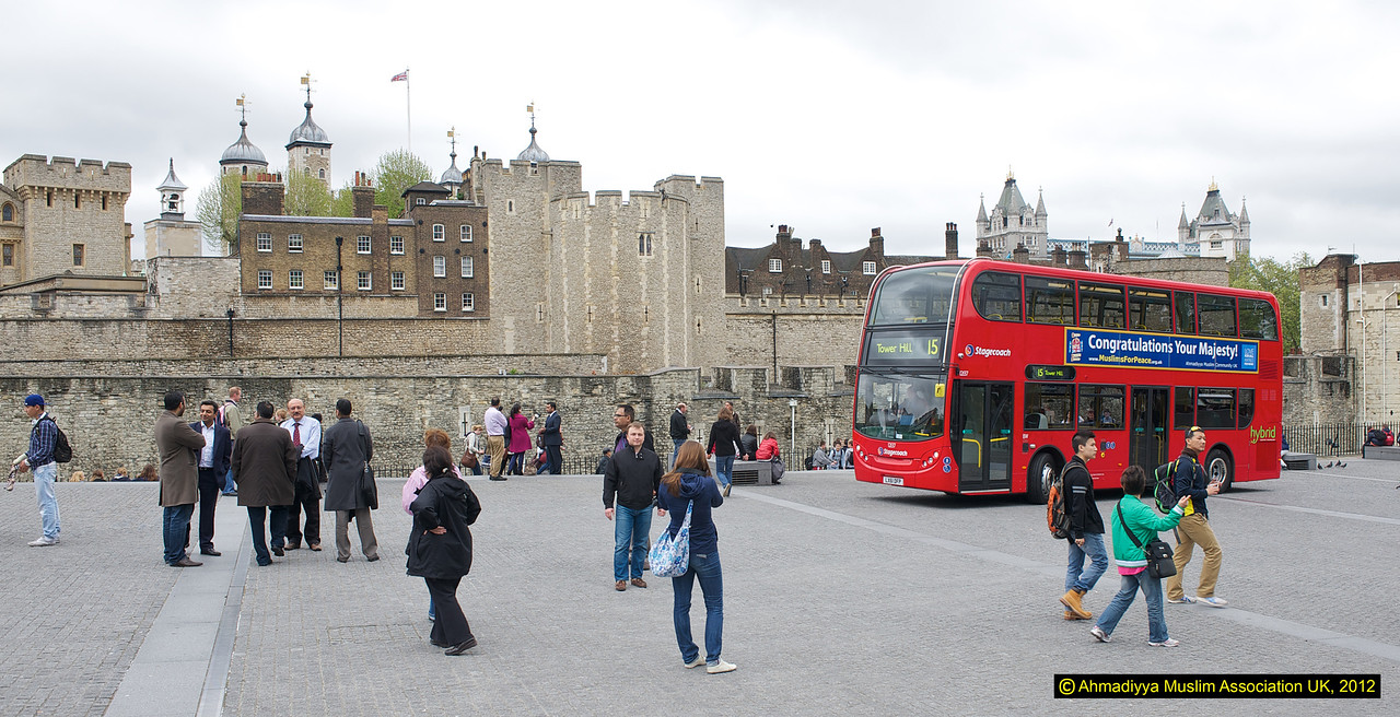 Jubilee/Message of peace bus outside Tower of London and just above the bus you can see the top of Tower Bridge - another major landmark of London