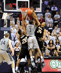 Georgetown's Mikael Hopkins (3) goes up against Towson's Jerrelle Benimon (20) and Bilal Dixon (24)