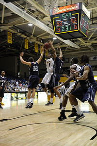 Marcus Damas, Towson (#1), goes up strong against UNC-Wilmington's Tanner Milson (12) and Donte Morales.