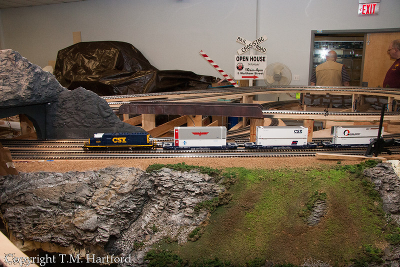 CSX doublestack freight led by a SD-40-2 is on the subway, near a recently mostly finished section of scenery.