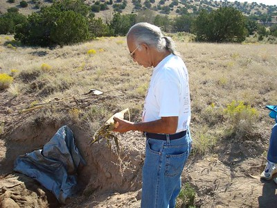 Pueblo elder, Phillip Duran receives the blessing of the roasted corn.