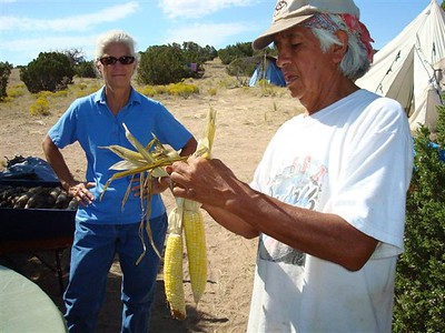 Pueblo elder, Larry Littlebird teaches us to braid corn in pairs for drying.