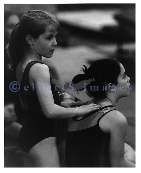 Two gymnasts relax before their turn at a gymnastics meet.