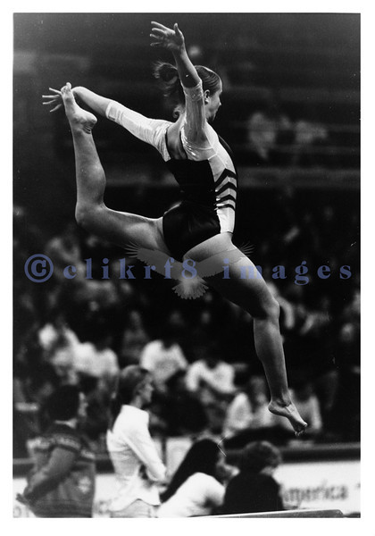 UW gymnastics meet in 2002 featuring a UW gymnast performing a stag leap as part of her beam routine. This was shot with available light with B&W film.