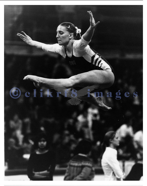 UW gymnastics meet in 2002 featuring a UW gymnast performing a tuck leap as part of her beam routine. This was shot with available light with B&W film.