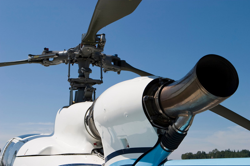 A stationary helicopter shows details of its engine and rotor blade assembly.