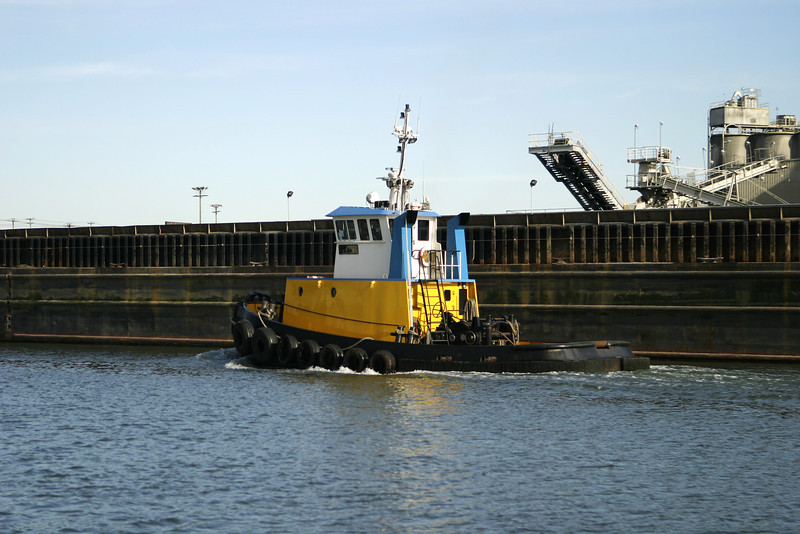 A yellow tugboat chugging away alongside a wharf in the Seattle harbor.