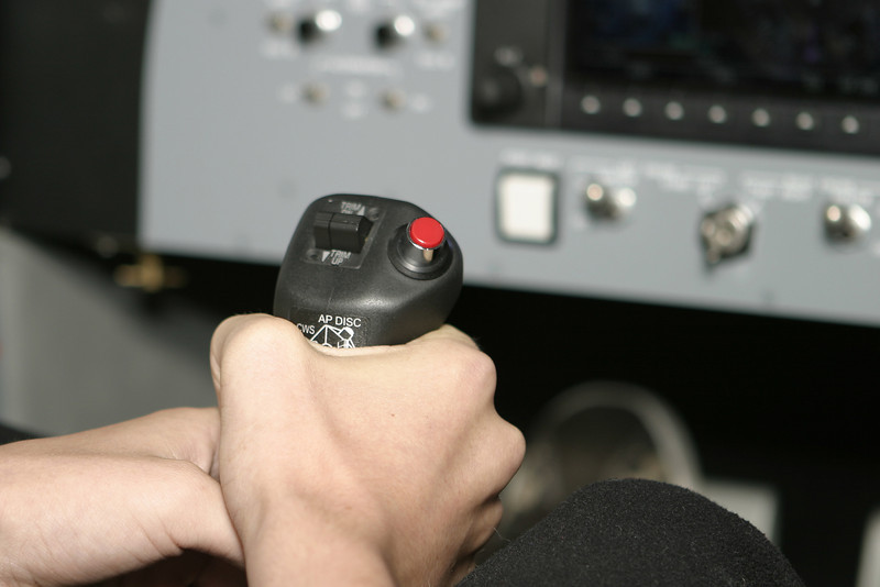 A hand gripping the controls for an aircraft. This photograph was taken in a flight simulator.