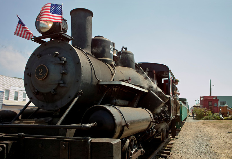 An old steam engine, waiting at a train station for people to get on or off the cars at the back. The engineer is looking out the engine cab back towards the people. The train is located in the town of Rockaway on the Oregon Coast.