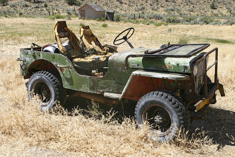 An old jeep that has been abandoned to rust and fall apart in a remote field near the Oregon desert.