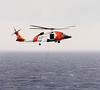 A United States Coast Guard helicopter lowering a rescue basket during an air-to-sea rescue mission. The Blackhawk copter was hovering over the bow of a cruise ship while evacuating an ill passenger.