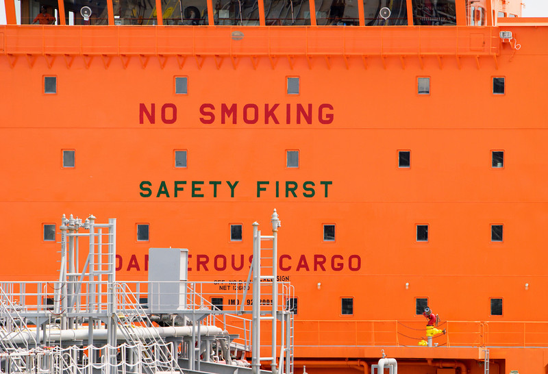 An enormous No Smoking sign on the bright orange bridge tower of an oil or gas tanker ship.